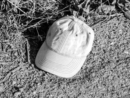 A person's baseball cap sits at the side of the road, abandoned, waiting to be rescued by a new owner.