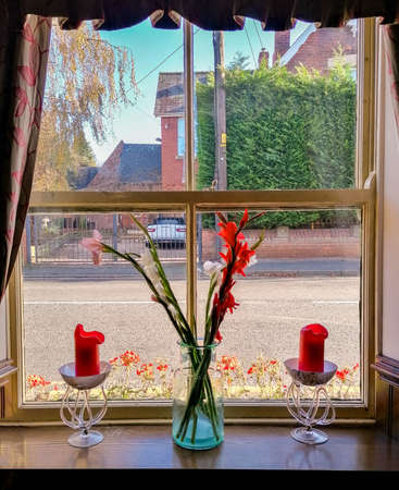 A lovely restaurant window setting with candles and flower, with a street view outside. Foto de archivo