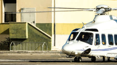 A luxury helicopter sits rotors running as it completes it's final checks before departing.