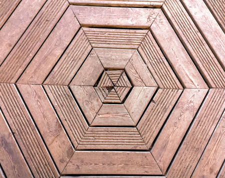 A wooden floor with hexagonal shapes. The floor well worn from years of use.