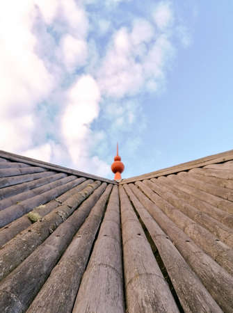 A sloping wooden rooftop with a small spire at the top. Behind is the blue skies above.