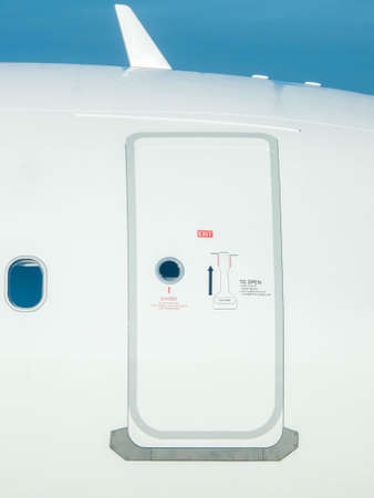 A closed door at the side of a large airline aircraft. The door secured to prevent unwanted pests or passengers from getting on board.
