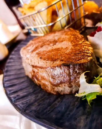 A scrumptious thick and well cooked fillet steak, served with chips and sauce. The fillet steak one of the most popular meat meals people enjoy. Foto de archivo