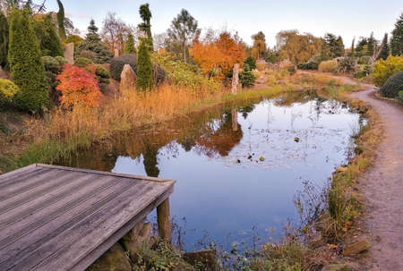 A small pond in well kept gardens with a small wooden walkway for viewers to stand and take in the scenery. Taken during autumn.