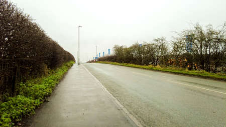 January 19, 2021 – Foxby Hill, Gainsborough, United Kingdom. A wet road on a steep incline, seen from the view of person walking up the path that runs alongside it. Stock Photo