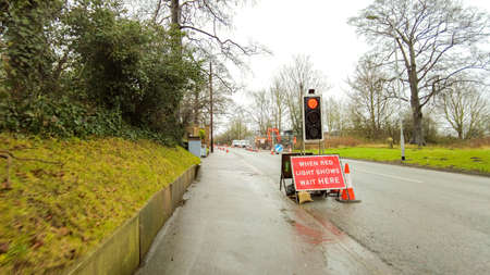 Roadworks being carried out on a steep incline of road. Signs and control measures in place to keep control of the traffic going up and down the road. Stock Photo