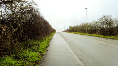 A wet road on a steep incline, seen from the view of person walking up the path that runs alongside it.