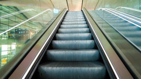 Long and steep escalators from the bottom looking upwards as a person is about to travel from the ground level up to the next floor.