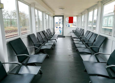 A row of seats inside a shelter for passengers or people to stop, rest and / or wait for their transport to pick them up.