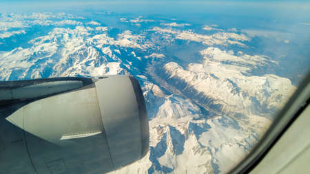 A view from a passenger window of a large aircraft traveling across the world on a holiday or business trip. The view of the awe inspiring French Alp mountains. Stock Photo