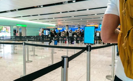 A long que of passengers waiting to get through passport control, in the United Kingdom.