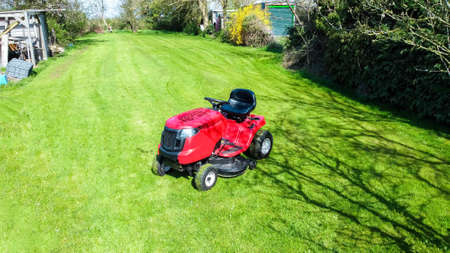 A view of a large ride along lawn mower cutting the grass of a large garden, at the back of a small property. The sun shining above during spring time.