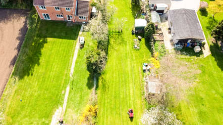 A long garden at the rear of a small property, in England, United Kingdom. The view seen from a drone high up above the property.