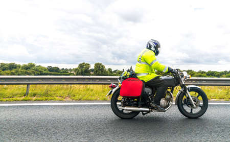 A vintage motorbike traveling alone one of the main United Kingdom motorways, seen from the side on view.