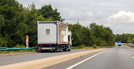 A large HGV vehicle traveling carrying a portacabin to be delivered or has just been collected from factory or customer parked up in a lay by on the side of a motorway or dual carriageway in United Kingdom. Standard-Bild
