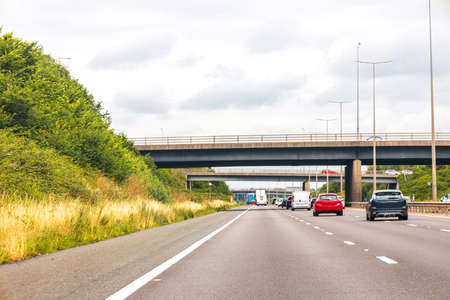 A motorway view of an upcoming bridge overhead, in the United Kingdom.