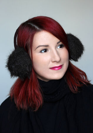 ear muffs: Redhead girl in the fur ear muffs and black scarf Stock Photo