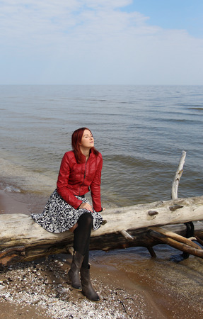latvia girls: The redhead girl sitting on the old tree at the see shore