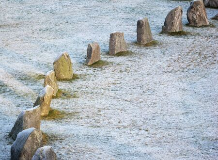 Ic: The big stones standing in the snow field in winter