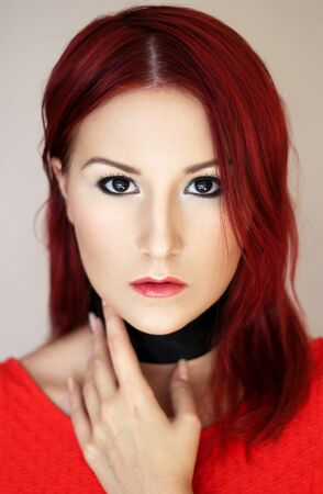 sexy redhead: Sexy redhead young woman in red top and with black ribbon on the neck portrait Stock Photo