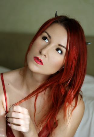 sexy redhead: Sexy redhead young woman with devil horns in the bedroom Stock Photo