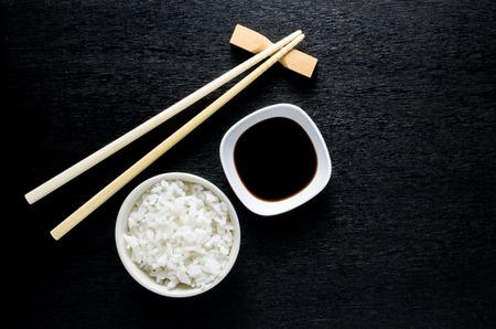 sauce bowl: Japanese sushi chopsticks over soy sauce bowl, rice on black background