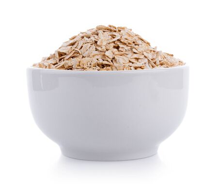 Tas de flocons d'avoine dans un bol blanc sur blanc