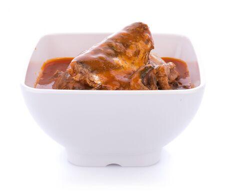 Sardines in tomato sauce on white bowl