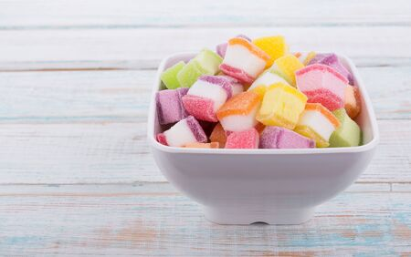 closeup colorful candy and jelly sweet in bowl on wooden Banco de Imagens