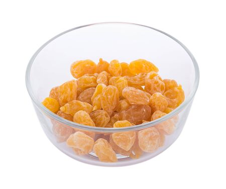 Dry yellow plums in bowl on white background