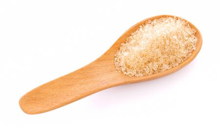 Brown sugar in spoon on white background