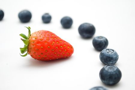 Red strawberry pointing to blueberries Stock Photo - 4657926
