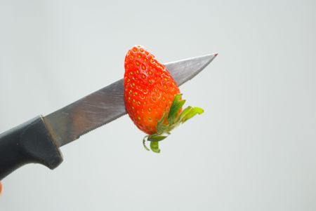 penetrating: Knife penetrating red strawberry