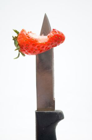 penetrated: Knife penetrating eaten red strawberry