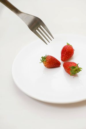 fragaria: Strawberries and silver fork on white plate