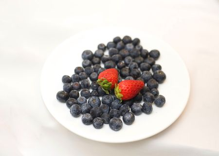 Two red strawberry on blueberries photo