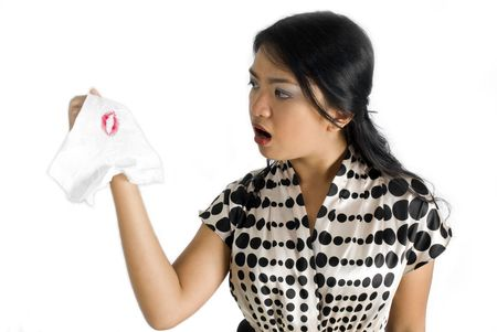 Side view of asian female holding napkin with lipstick stain shocked