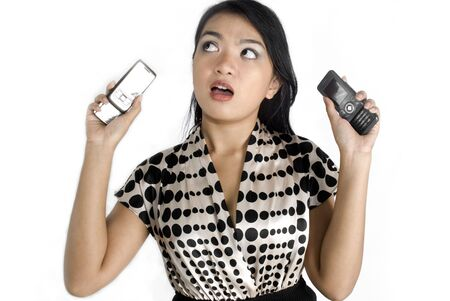 Female asian business Female asian business woman shocked with a pair of mobile phones photo