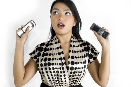 Female asian business woman shocked with a pair of mobile phones photo