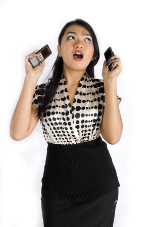 Female asian business woman shocked and busy with a pair of mobile phones photo