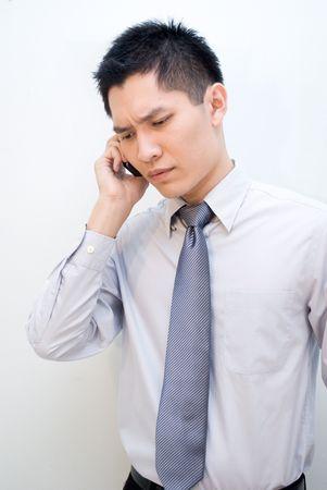 constipated: Hombres de negocios asi�ticos hablando por tel�fono Foto de archivo