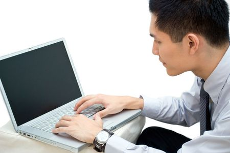 Side profile shot of Asian business male working on laptop