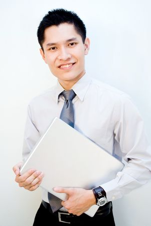 Confident Asian business male carrying laptop Stock Photo