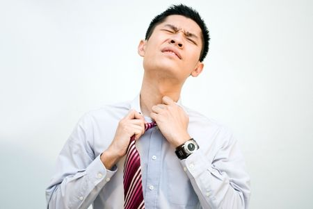 constipated: Asian business man loosening tie, stress