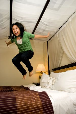 Asian girl jumping on bed