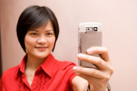 Asian lady looking at mobile phone - videocall photo