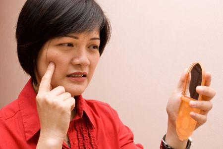 Asian lady touching face with worried expression Stock Photo