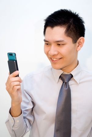 Asian guy looking at mobile phone photo