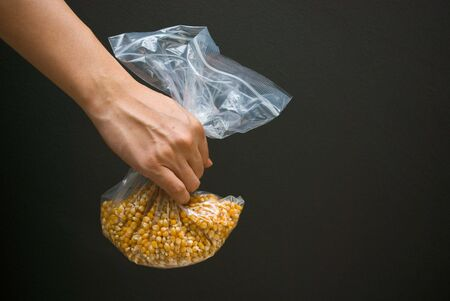 Arm Holding a bag of raw corn kernel photo