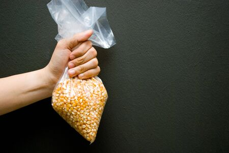 Hand holding a bag of corn kernel photo